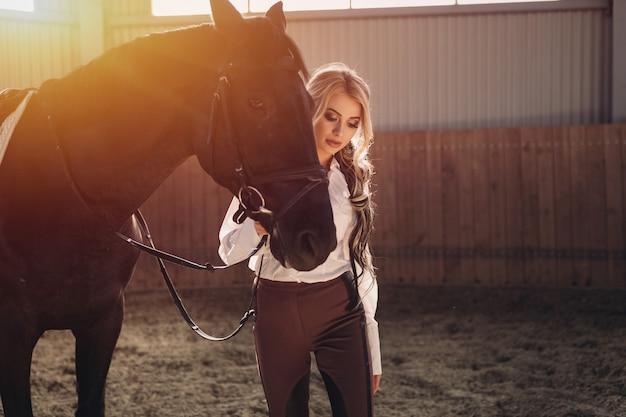 Linda elegante jovem loira em pé perto de seu cavalo vestindo uniforme concorrência