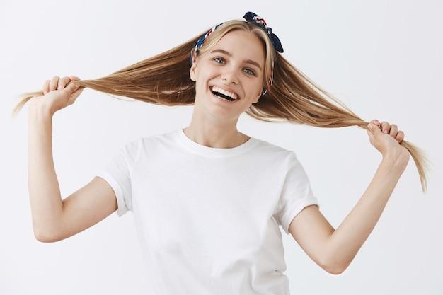 Linda elegante jovem loira posando contra a parede branca