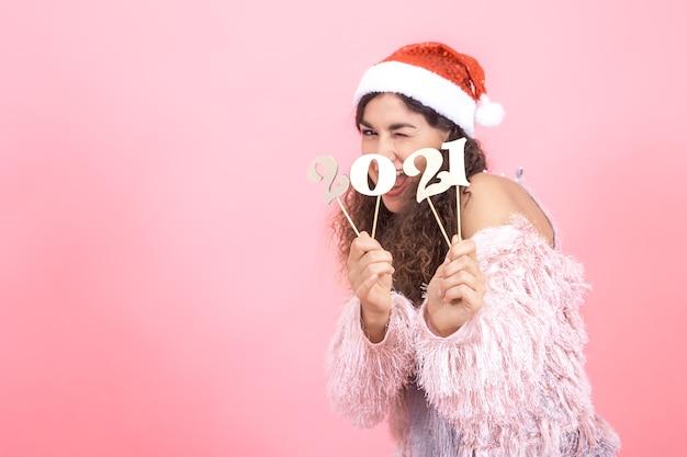 Linda elegante jovem morena com cabelo encaracolado em um boné de natal em um fundo rosa de estúdio posando com um número de madeira para o conceito de ano novo