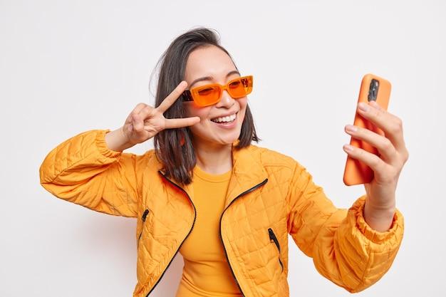 Linda elegante mulher asiática leva selfie no celular faz o sinal v sorrisos tem rosto positivo usa óculos de sol laranja e jaqueta isolada sobre uma parede branca. estilo de vida moderno