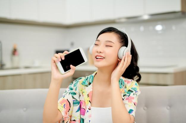 Linda emocional feliz jovem no sofá em casa ouvindo música com fones de ouvido segurando o canto do telefone móvel.