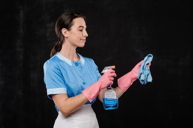 Linda empregada de hotel com uniforme e luvas de borracha rosa borrifando detergente no espanador na frente da câmera contra um fundo preto