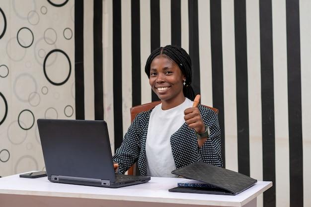 Linda empresária africana se sentindo animada enquanto fazia o polegar para cima