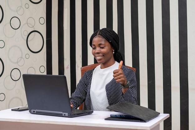 Linda empresária africana se sentindo animada enquanto trabalha no escritório e fez sinal de positivo