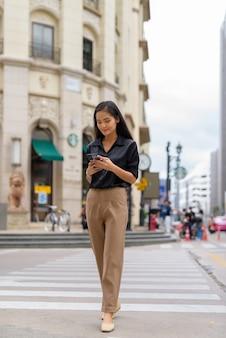 Linda empresária asiática caminhando ao ar livre na rua da cidade usando telefone celular e mensagens de texto