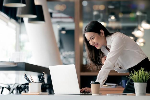 Linda empresária asiática comemorar ao usar o laptop no escritório e mostrando prazer.