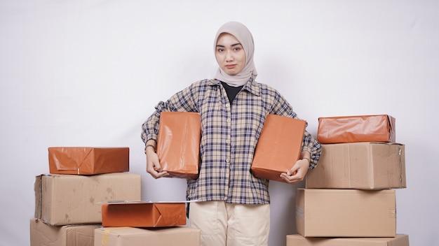 Linda empresária asiática mostrando pacotes felizmente isolados no fundo branco