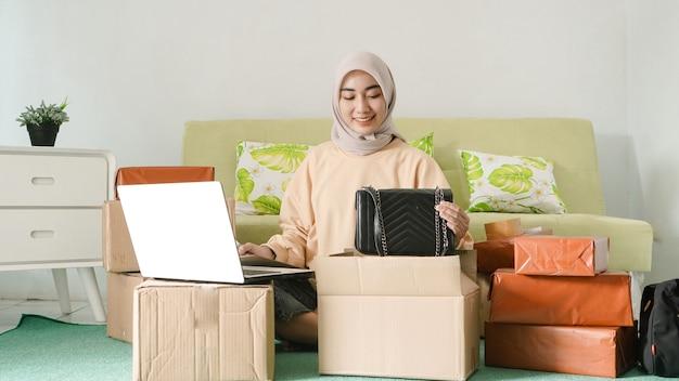 Linda empresária asiática preparando produtos para vender na sala