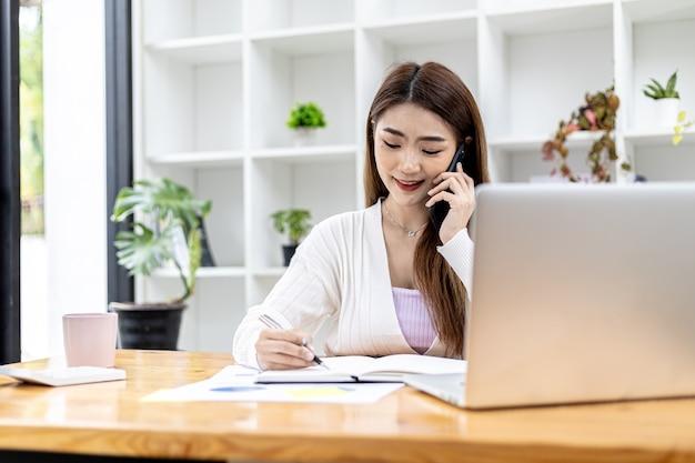Linda empresária asiática sentada em seu quarto, conversando com seu parceiro via celular e verificando documentos financeiros, ela é uma executiva de uma empresa iniciante. gestão financeira.