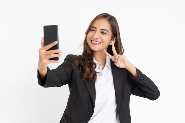 Linda empresária asiática sorrindo ao tirar uma selfie usando o celular