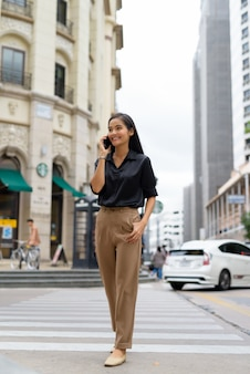 Linda empresária asiática sorrindo e falando ao telefone ao ar livre na rua da cidade enquanto caminha