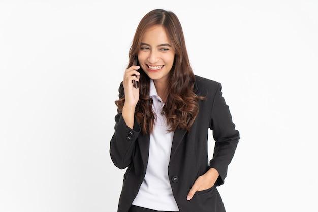 Linda empresária asiática sorrindo, ouvindo uma chamada usando um telefone celular, feliz com copyspace