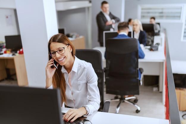 Linda empresária caucasiana com roupa formal, usando o computador e falando ao telefone. no fundo, seus colegas de trabalho trabalhando.