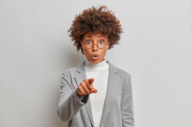 Linda empresária de cabelos cacheados impressionada aponta diretamente com o dedo indicador, vê algo surpreendente na frente, usa roupa formal