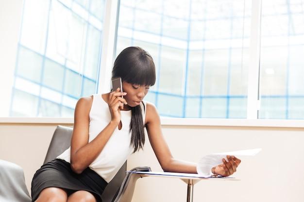 Linda empresária falando ao telefone e lendo jornal no escritório