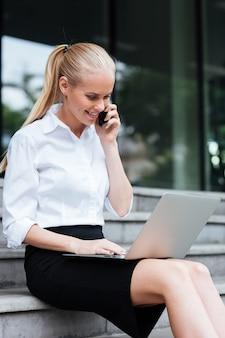 Linda empresária falando no telefone e usando o laptop enquanto está sentada na escada ao ar livre