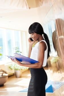 Linda empresária lendo jornais e falando ao telefone no escritório