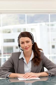 Linda empresária no telefone com fone de ouvido sentado em uma mesa