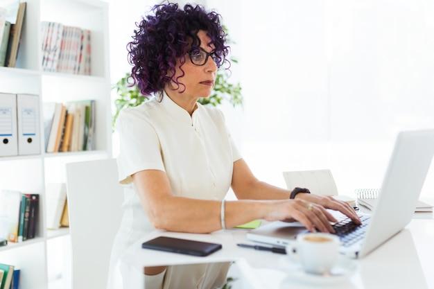 Linda empresária trabalhando com o laptop no escritório.