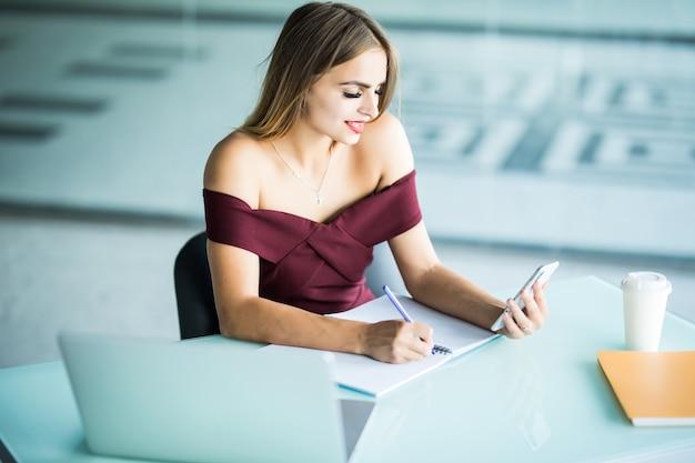Linda empresária trabalhando sentada em sua mesa no escritório