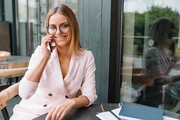 Linda empresária usando o telefone em um café