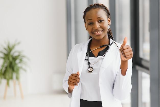 Linda enfermeira afro-americana de braços cruzados