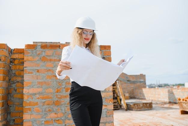 Linda engenheira está revisando os planos de uma obra
