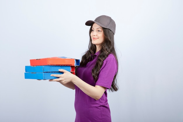 Linda entregadora de uniforme roxo, dando caixas de pizza. foto de alta qualidade