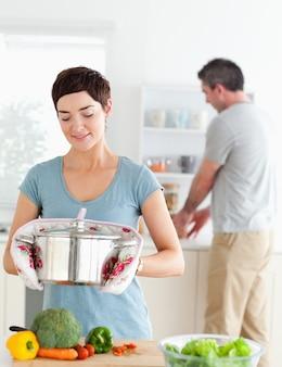 Linda esposa segurando uma panela enquanto o marido está lavando a louça