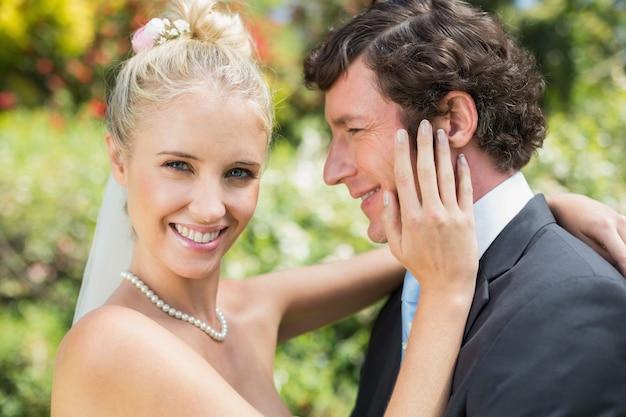 Linda esposa tocando sua nova bochecha de maridos sorrindo na câmera