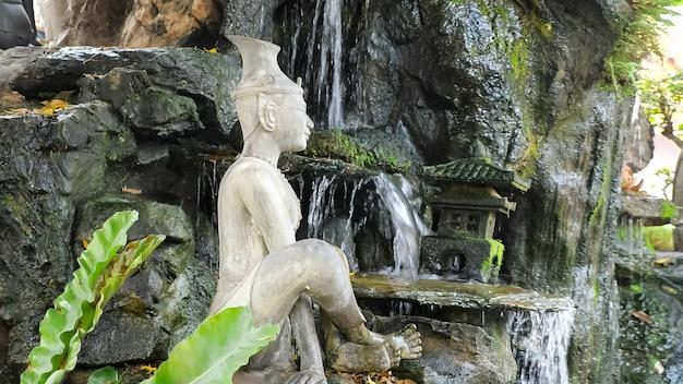 Linda estátua de buda meditando em pedra branca perto de uma cachoeira artificial sobre rochas com grama verde e um pequeno templo em modelo