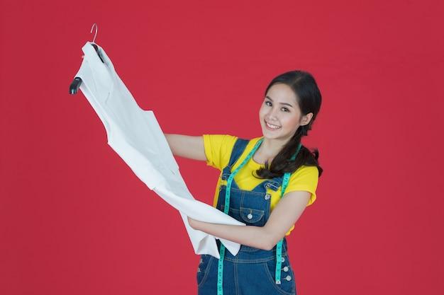 Linda estilista asiática feminina em suas mãos está o vestido branco que ela desenhou e costurou sozinha. ela sorri orgulhosamente isolada sobre fundo vermelho.