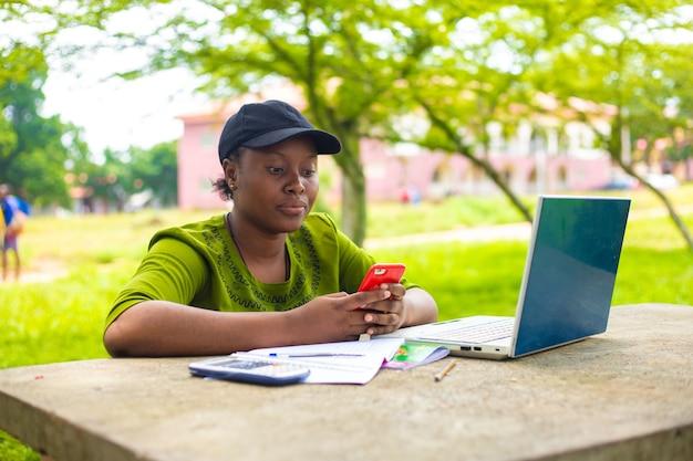 Linda estudante africana estudante universitária usando laptop ao ar livre