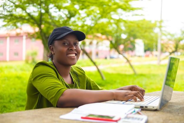 Linda estudante africana sorrindo usando seu laptop no campus