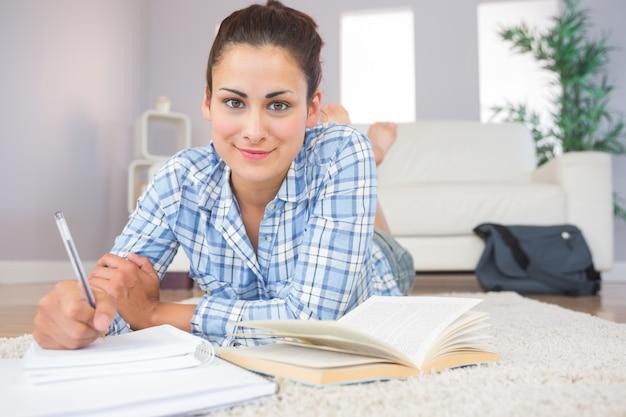 Linda estudante sorridente fazendo a lição de casa no chão na sala de estar
