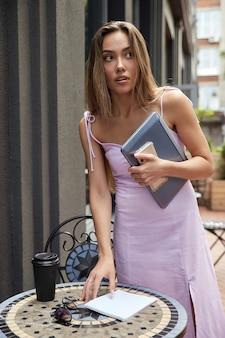Linda estudante tomando uma xícara de café do lado de fora do café segurando um laptop e um telefone