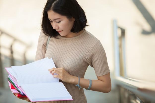 Linda faculdade feminina asiática olhando seu livro em pé ao ar livre