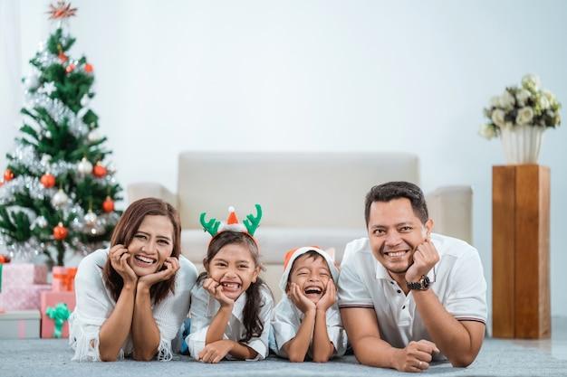 Linda família asiática com árvore de natal na sala de estar