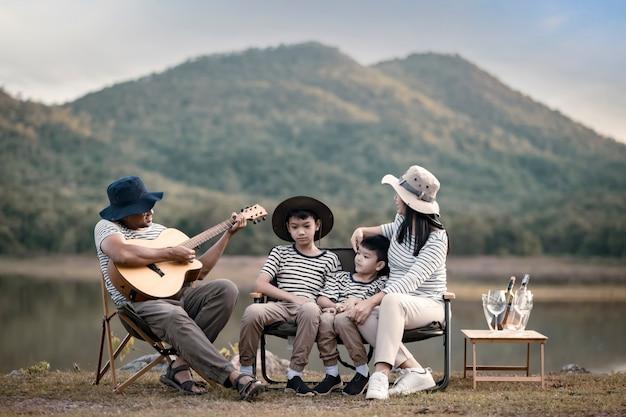 Linda família asiática fazendo piquenique e na festa de verão da páscoa em um pasto perto do lago e da montanha. férias e férias. estilo de vida das pessoas e o conceito de vida familiar feliz.