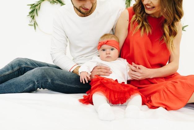 Linda família caucasiana de mãe, pai e filha sentada em trajes correspondentes