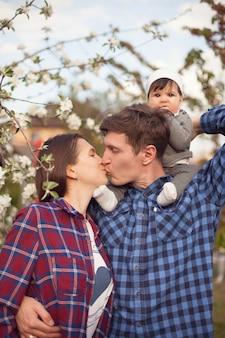 Linda família com camisas quadriculadas no fundo de uma macieira branca em flor