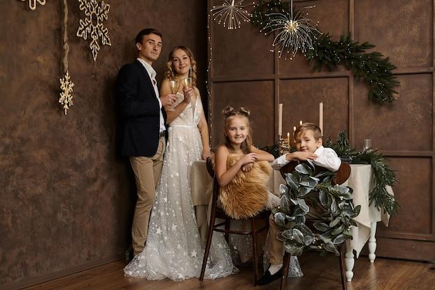 Linda família com dois filhos no quarto com decoração de natal