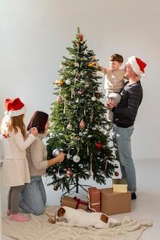 Linda família decorando árvore de natal