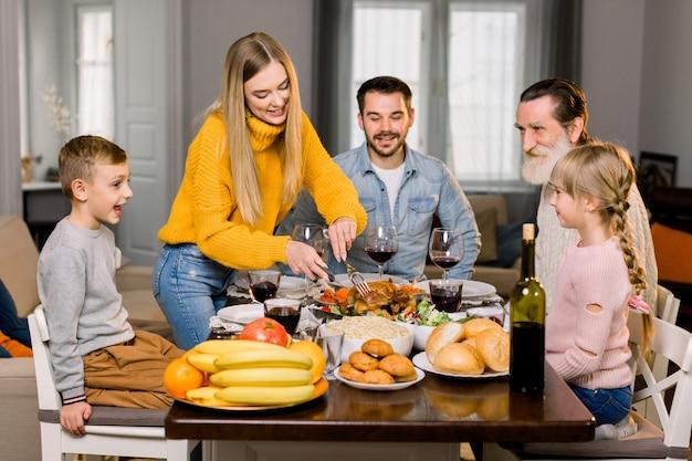 Linda família feliz, avô, pais e filhos, comemorando o dia de ação de graças juntos