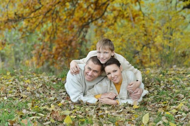 Linda família feliz deitada no parque de outono