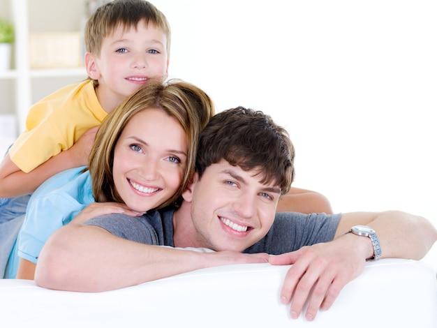 Linda família feliz e sorridente de três pessoas com filho pequeno - dentro de casa