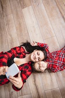 Linda família feliz mãe e filha feliz fazendo selfie no celular juntas em casa