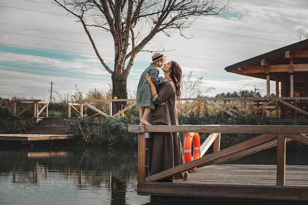 Linda família feliz, mãe e filha juntas em um píer de madeira na margem do lago