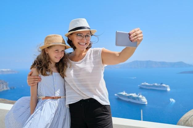 Linda família feliz, mãe e filha viajando juntos no mediterrâneo. tirando selfie usando smartphone, bela paisagem cênica com fundo de navios de cruzeiro, espaço de cópia