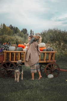 Linda família feliz, mãe, filha e cachorro de estimação juntos em um carrinho de madeira com abóboras